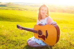Young female left-handed musician playing guitar instrument at nature royalty free stock photos