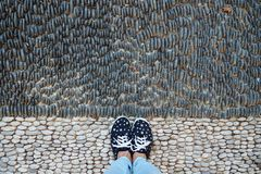 Female legs in sneakers and jeans, on the road paved with stones stock photo