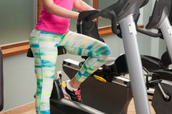 Young female legs training and riding the stationary bicycle Stock Photos