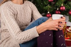 Female in sweater holding cup of coffee on legs knees and Christmas tree and present boxes in background. Young female legs with warmers on floor carpet holding Royalty Free Stock Images