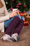 Female sitting on carpet floor and holding cup of coffee in hands on legs with warmers and Christmas tree in background. Young female legs with warmers on floor Stock Photography