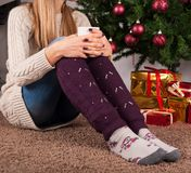 Young girl sitting on floor and holding cup of coffee in hands on legs with warmers and Christmas tree in background. Young female legs with warmers on floor Stock Image
