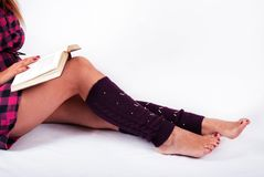 Young female legs with warmers and girl holding book on knees. Young female in plaid shirt reading book and legs with warmers on white background. Close up stock images