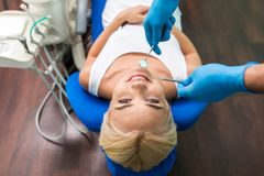 Young female lies in the dental chair and smile stock photos