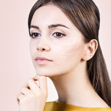 Young female with lifting arrows. Young female face with clean fresh skin over biege background. Antiaging concept Stock Image