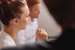 Young female listening to presentation in conference room Royalty Free Stock Photo