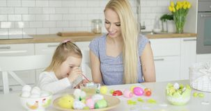 Young female and little girl painting eggs stock footage