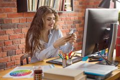 Young female with long hair working at home or in a loft style office. She chatting via smartphone and smiling. Designer, editor, royalty free stock photography
