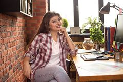 Young female with long hair working at home or in a loft style office. She wear urban clothes and smiling stock images