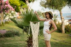 Young female holding piece of macrame in her hands. Young female with long straight hair, wearing white top and beige shorts holding a pice of macrame wall art Royalty Free Stock Photography
