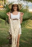 Young female holding piece of macrame in her hands. Young female with long straight hair, wearing white top and beige shorts holding a pice of macrame wall art Royalty Free Stock Images