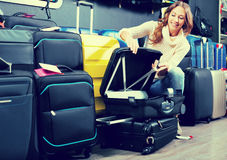 Young female looking at roll-aboard bags Stock Image