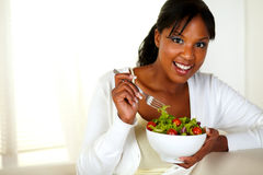 Young female looking at you while eating salad. Portrait of a young female looking at you while eating salad at home indoor. With copyspace Royalty Free Stock Photos