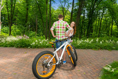 Young female looks out from a guy  after biking in a park Royalty Free Stock Photo