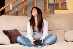 Young female lose playing video-games. Concentrating on sofa at home royalty free stock photo