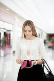 Young female lost money. Upset young woman in shopping mall checking her purse with troubled look. Out of money, broke Royalty Free Stock Photo