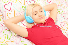 Young female lying on a bed and listening music Stock Images