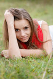 Young female lying down on grass Stock Images