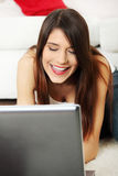 Young female lying on floor using laptop. Stock Image