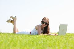 Young female lying on the grass in the park. A cute young female lying on the grass in the park using a laptop royalty free stock images