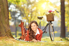 Young female lying on a green grass with bicycle on a sunny day Royalty Free Stock Images