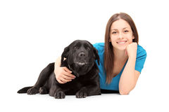 A young female lying and posing with a black dog Stock Image