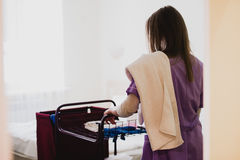 Young Female Maid pushing cart While Cleaning Hotel Rooms Stock Image