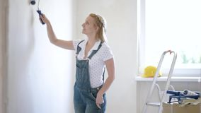 Woman makes repairs in flat. Young female makes repairs in new flat. Beautiful woman - painting wall in apartment. Woman doing overhaul of house. Girl making stock video