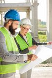 Young male and female architects or business partners looking at floor plans on a construction site. Young female and male engineers or business partners at stock photo