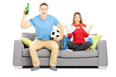 Young female and male football supporters cheering Royalty Free Stock Photography