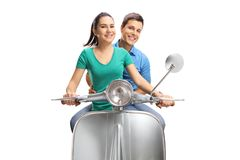 Young female and male riding a vintage scooter stock image
