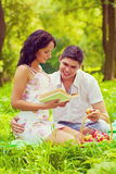 Young female and male sitting on grass smiling and writing the b Royalty Free Stock Photography