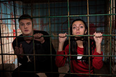 Young female and male victims imprisoned in a metal cage with a Royalty Free Stock Photography