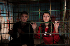 Young female and male victims imprisoned in a metal cage holding Stock Photos