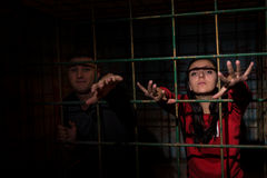 Young female and male victims imprisoned in a metal cage reachin Royalty Free Stock Photography