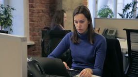 The young female manager in dark blue roll-neck sweater is working on computer. The professional. The young female manager in dark blue roll-neck sweater is stock video
