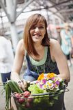 Young Female At Market Place. Female At Market Place With Basket Full Of Vegetables And Bouquet Of Flowers stock images