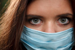 Young female in mask. Macro of young female in mask looking at camera Royalty Free Stock Images