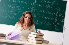 The young female math teacher in front of chalkboard. Young female math teacher in front of chalkboard royalty free stock photos