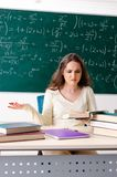 The young female math teacher in front of chalkboard. Young female math teacher in front of chalkboard stock photos