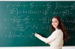 The young female math teacher in front of chalkboard. Young female math teacher in front of chalkboard royalty free stock images