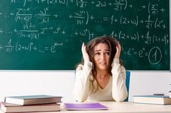 The young female math teacher in front of chalkboard. Young female math teacher in front of chalkboard royalty free stock photography