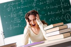 The young female math teacher in front of chalkboard. Young female math teacher in front of chalkboard stock image