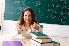 The young female math teacher in front of chalkboard. Young female math teacher in front of chalkboard royalty free stock photo