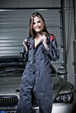 Young female mechanic. A young woman wearing a mechanics suit in a garage Royalty Free Stock Image