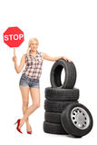 Young female mechanic holding a stop sign Stock Photo