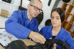 Young female mechanic inspecting piece repair shop. Young female mechanic inspecting a piece repair shop Royalty Free Stock Photo