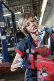 Young female mechanic in protective workwear working on machinery part in automobile repair shop Stock Photo