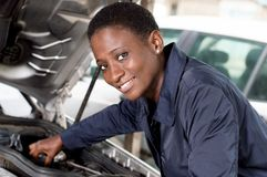 Young woman mechanic repairing a car. Young female mechanic repairs a car by putting the engine in good condition royalty free stock photos