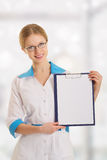 Young female medical doctor with clipboard. Smiling young female medical doctor with clipboard royalty free stock photos
